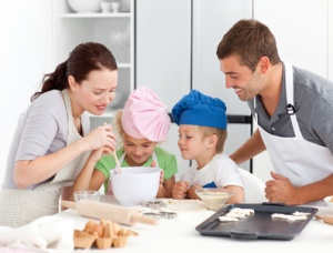 Adorable family baking together in the kitchen to make delicious cookies